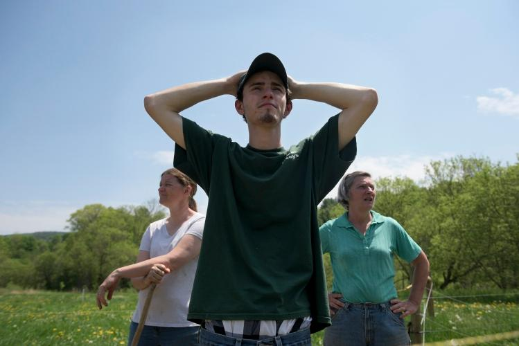 Matt Deome with his mother Amy (left) and Joan Wortman (right) looks over the Green Acres pasture after setting the cows to graze in South Randolph VT - photo by James Patterson Valley News