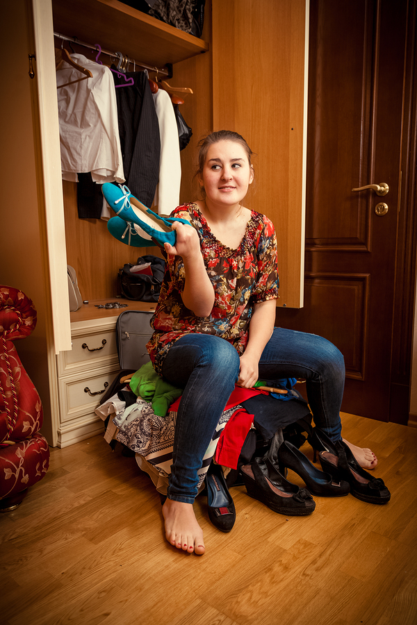Photo of young woman sitting on overfilled suitcase and holding shoe