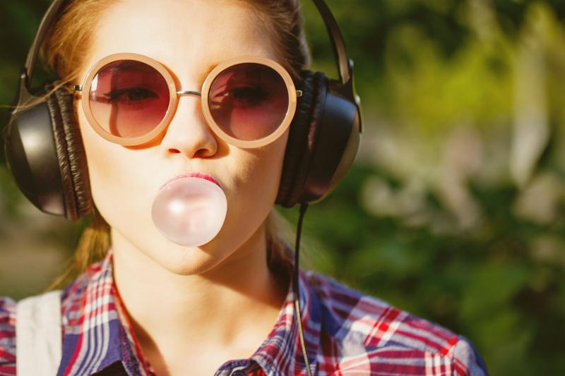Young hipster girl listening to music on headphones in a summer park. Portrait close-up with chewing gum. Warm toning. The concept of cheerful youth.
