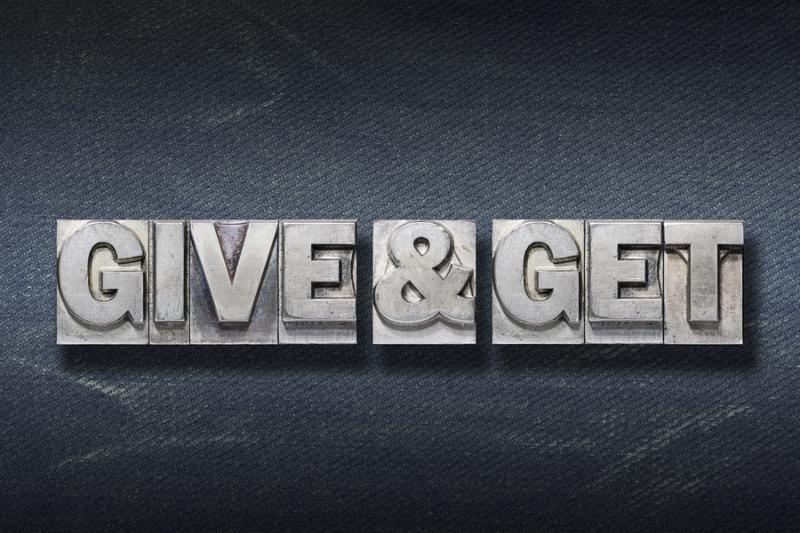 give and get phrase made from metallic letterpress on dark jeans background