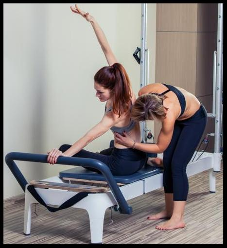 Pilates reformer workout exercises man with instructor  at gym indoor_