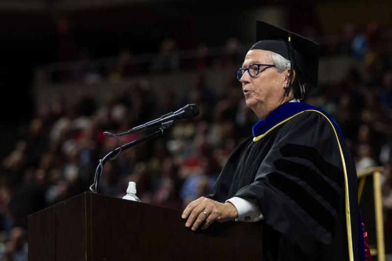 Kevin Cooney in cap and gown at podium delivering Fall 2017 commencement speech