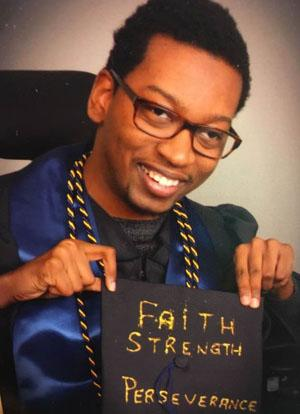 Taylor Boykin in his graduation outfit and holding his cap that says faith, strength, and perseverance