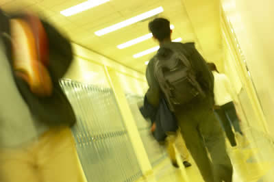 Student walking down hallway past lockers wearing backpack