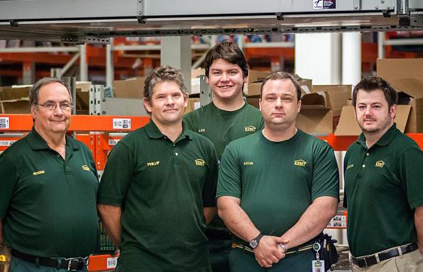 Employees at Kent Building Supplies stand in a warehouse smiling at the camera.