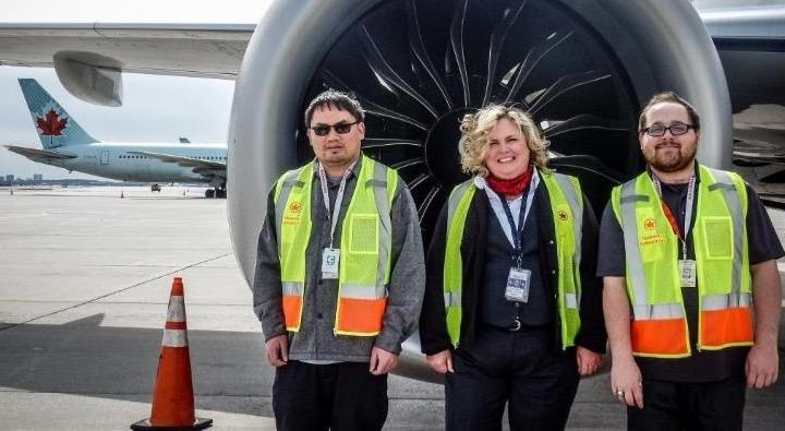 Female supervisor and two male RWA hires standing in front of plan engine.