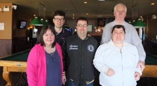 Shane surrounded by his family in a pool hall.