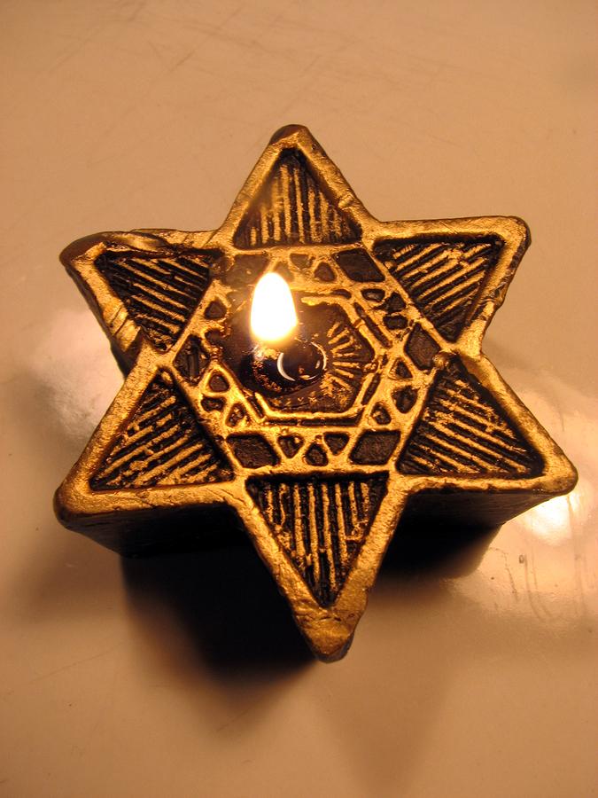 a star of david candle burns the the chanukah season.