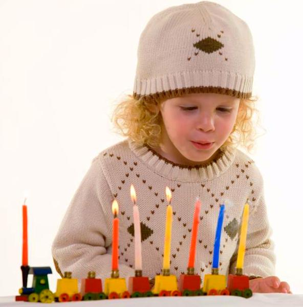 Young blond hair three year old boy lighting the candles in the Jewish tradition to celebrate Hanukkah