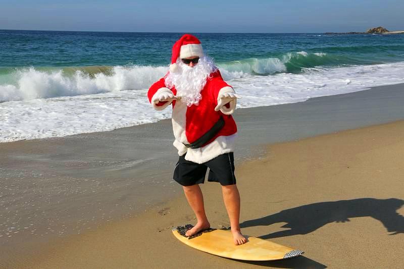 Surfing Santa. Santa Claus Surfs on his Surf Board while on a Beautiful Beach with a Blue Ocean. Focus on Santas Face Santa Vacation. Surfing Santa. Santa goes Surfing. Santa Claus enjoys the beach