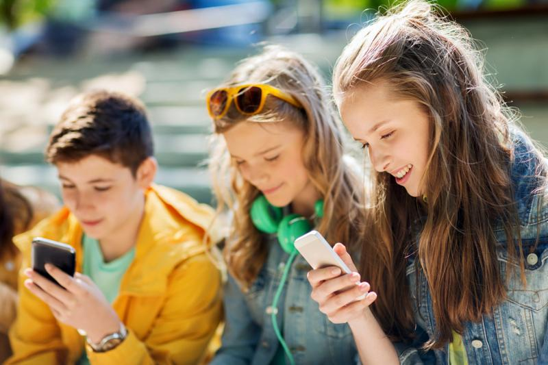 technology_ internet addiction and people concept - happy teenage friends with smartphones outdoors