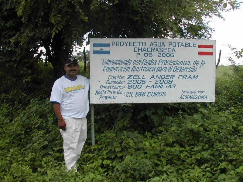 Juan Enrique stands in front of the potable water project sign in Chacraseca