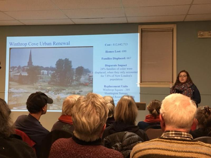 Woman giving presentation with slideshow to a crowd of people.