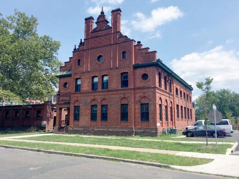 Photo of 60 Popieluszko Court, a three-story brick building with a parking lot to the right.