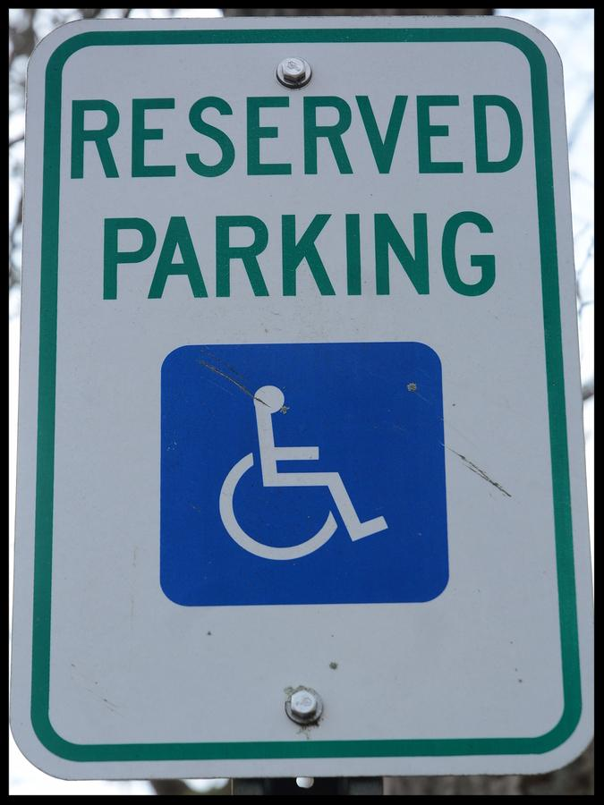 Handicap sign showing reserved parking, against the law to park there.     Note  Soft Focus at 100 , best at smaller sizes