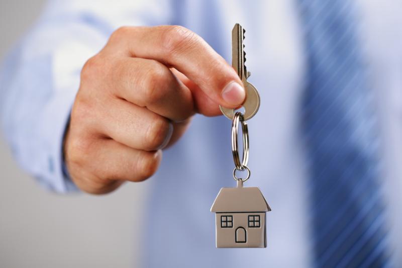 Hand holding a key, symbolic of homeownership.