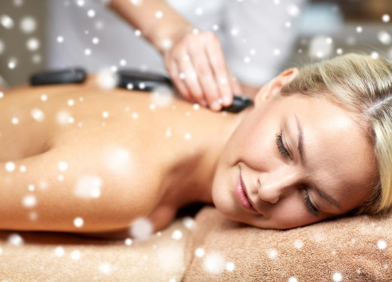 people, beauty, spa, healthy lifestyle and relaxation concept - close up of beautiful young woman having hot stone back massage in spa with snow effect