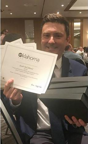 man holding certificates and plaques