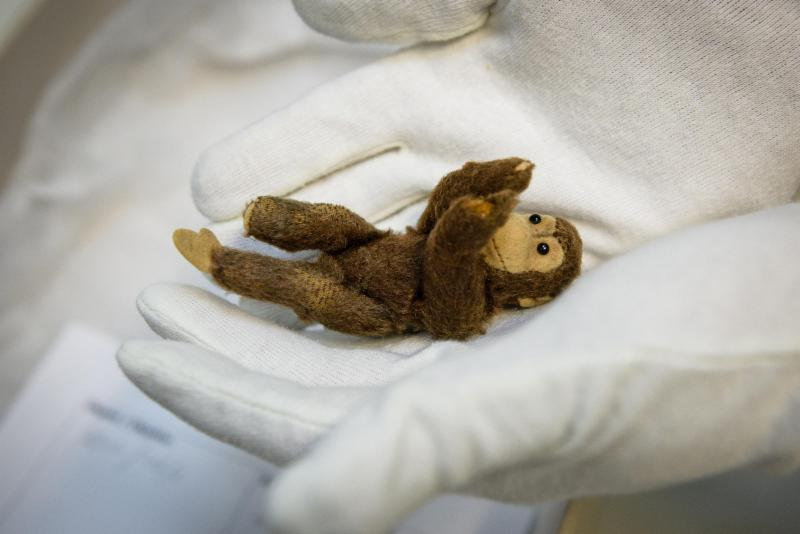 toy monkey cradled in gloved hands