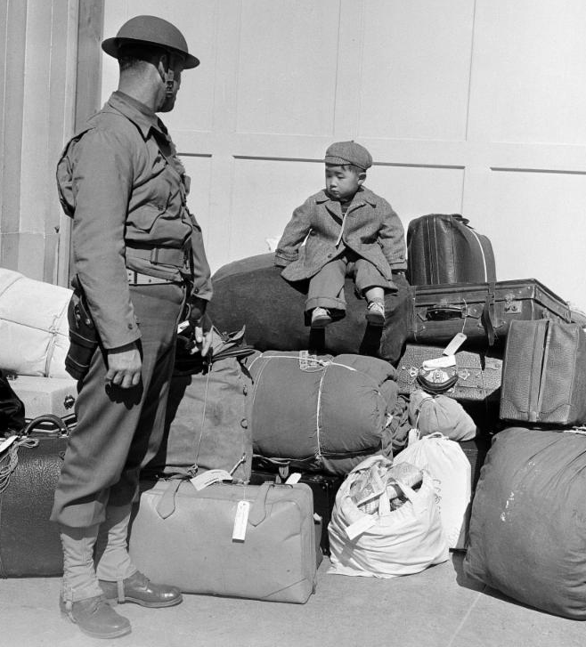soldier watches little boy on top of mound of luggage