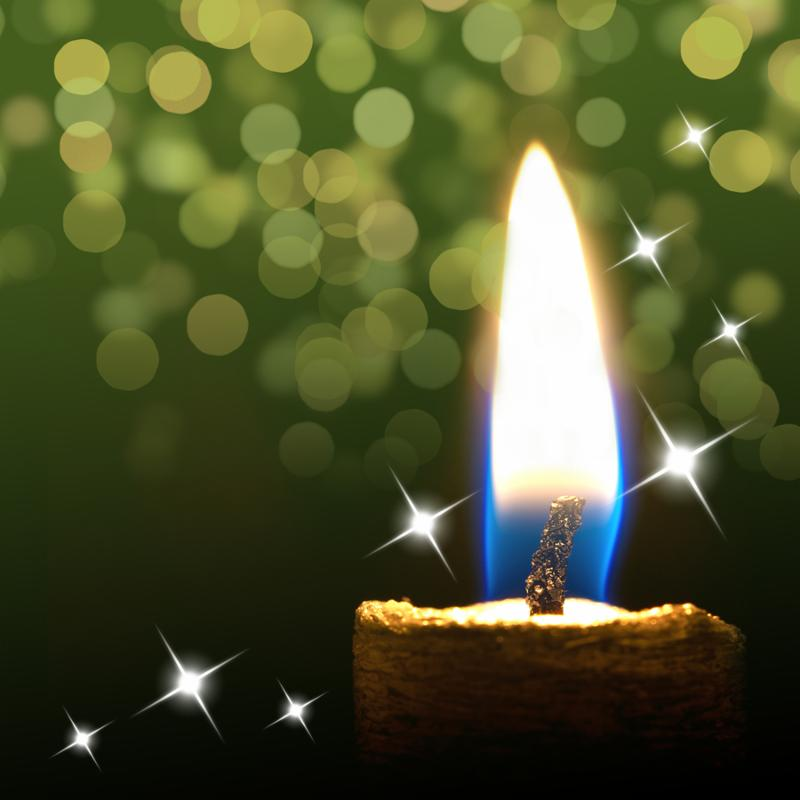 Burning candle on abstract green color background