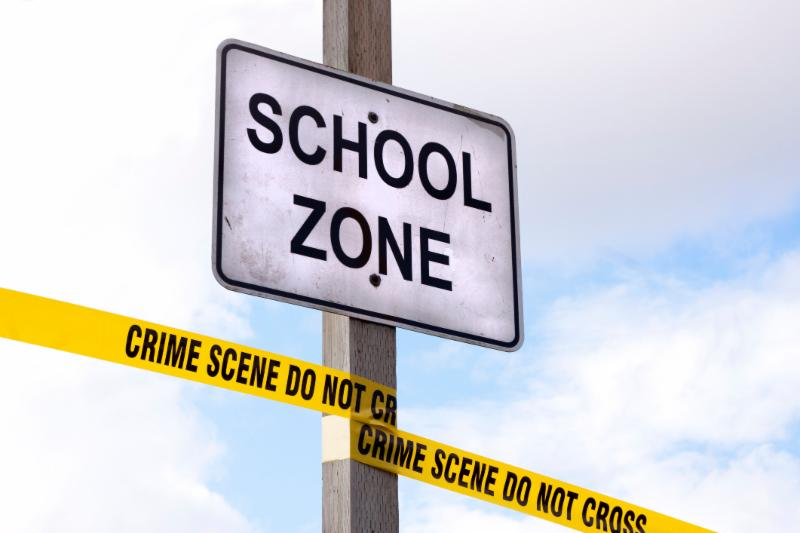school zone sign with yellow crime scene tape