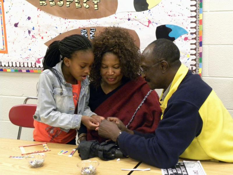 A student working on a craft with her grandparents at Grandparents Night.