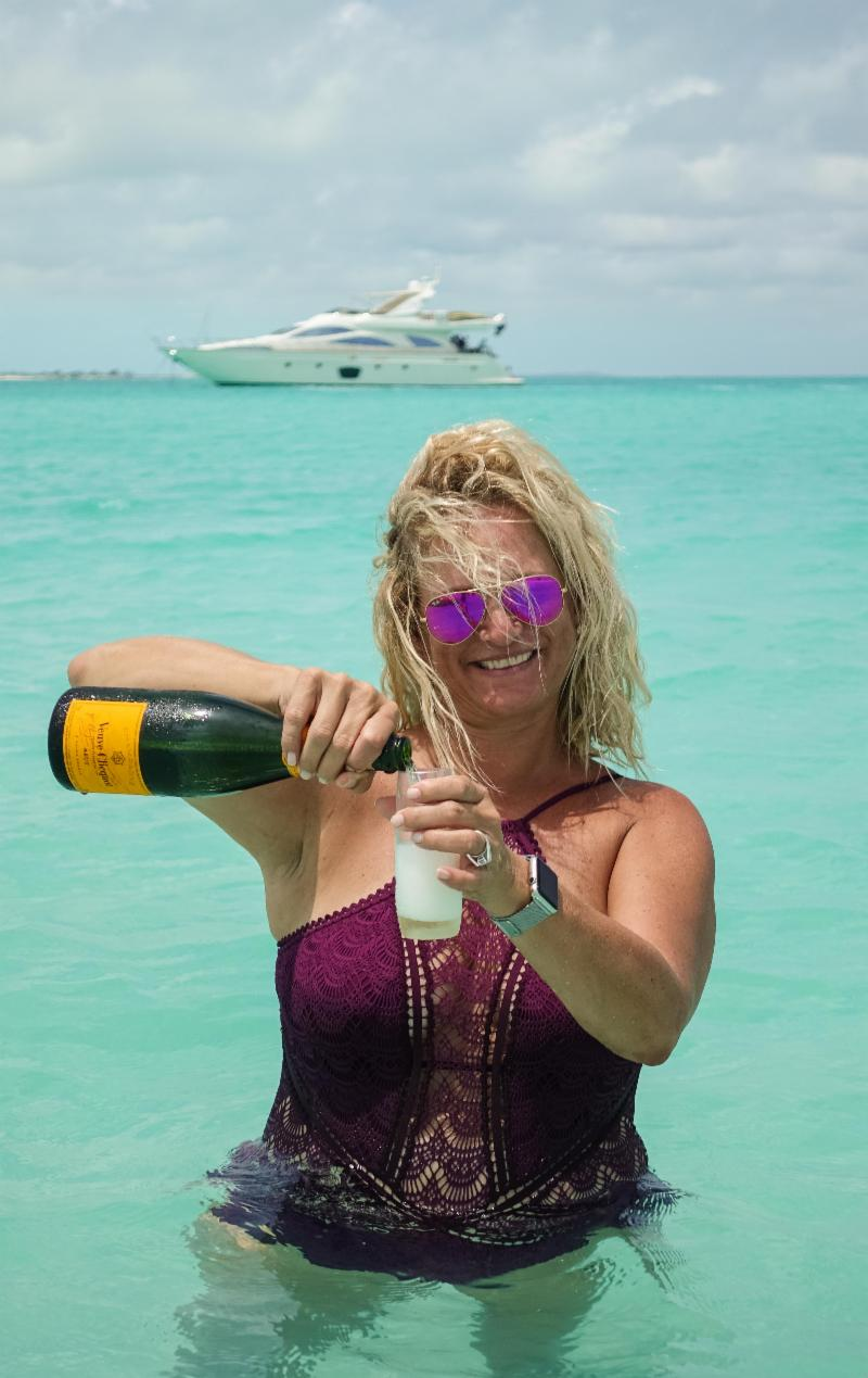 Malaka pours Champagne in front of yacht