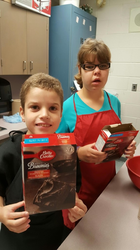 Male and female student holding brownie boxes