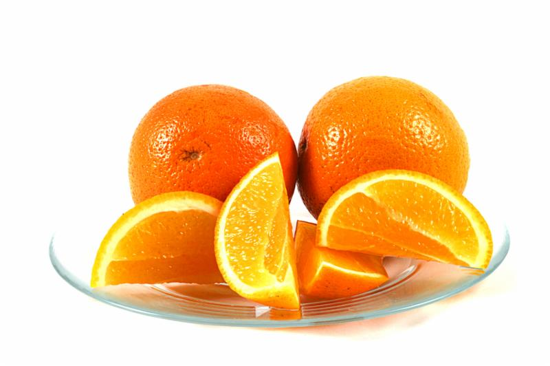 orange slices on a glass plate with a white background