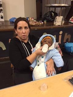 Volunteer feeding one of our diaper babies as her mother shops