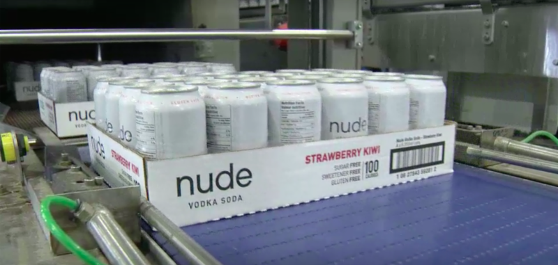 nude vodka soda cans on conveyor belt