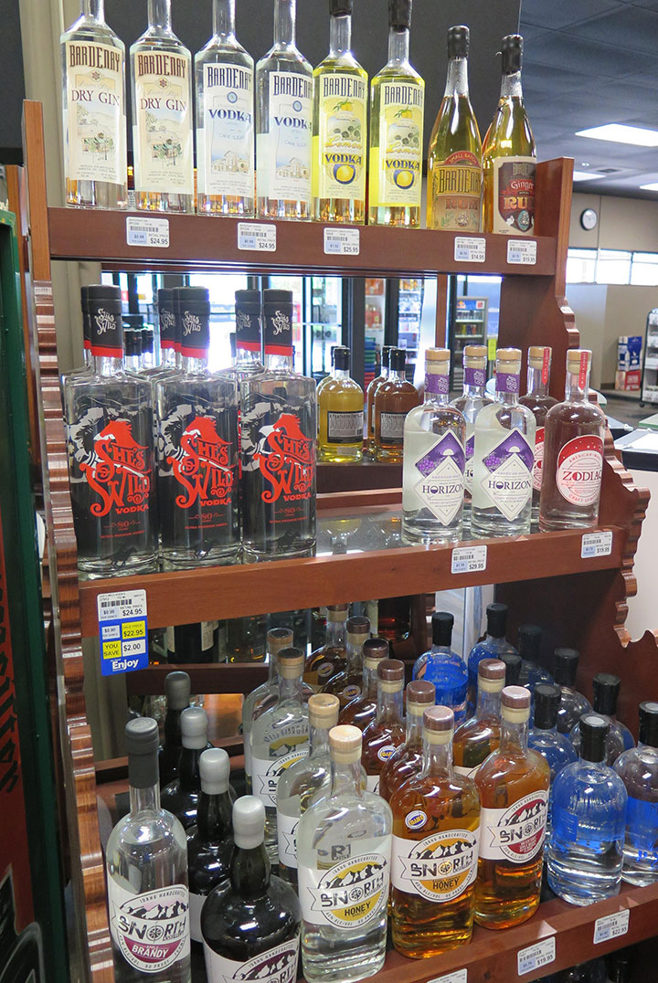 Idaho-made craft spirits are displayed on an Idaho-shaped shelf at a state liquor store in Boise