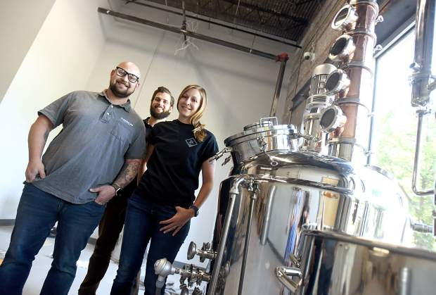 Trista Estrin_ right_ Matt Estrin_ left_ and Dan Moody_ stand by the distiller at Tower 56 Distillery_ 825 9th St. Unit B_ in downtown Greeley.