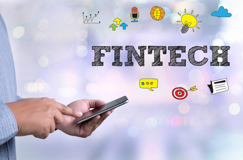 FINTECH Investment Financial Internet Technology person holding a smartphone on blurred cityscape background
