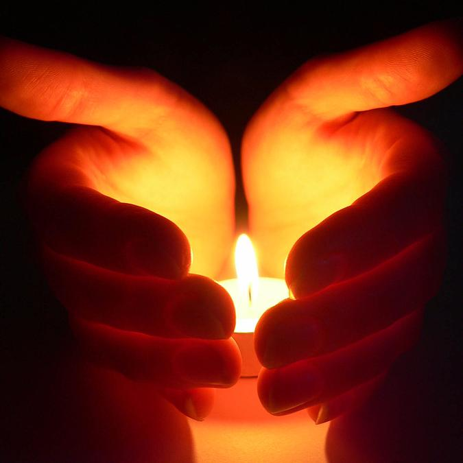 hands cupped around a candle