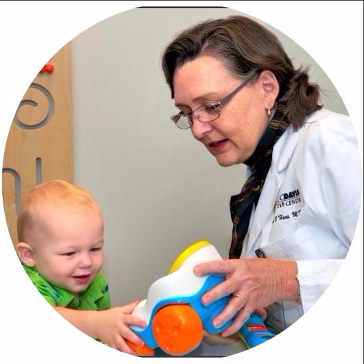 UC Davis pediatric ophthalmologist Dr. Mary O_Hara wears a lab coat while playing with a blue and orange toy with a toddler wearing a green shirt.