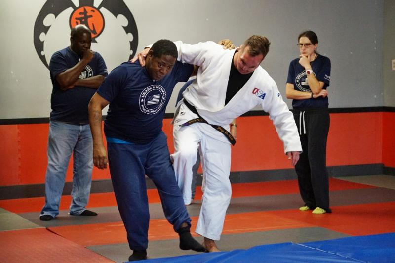 Society's Greg DeWall teaches judo to a man as a woman and man look on.