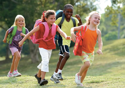 Kids in bright colors run across a field while wearing backpacks.