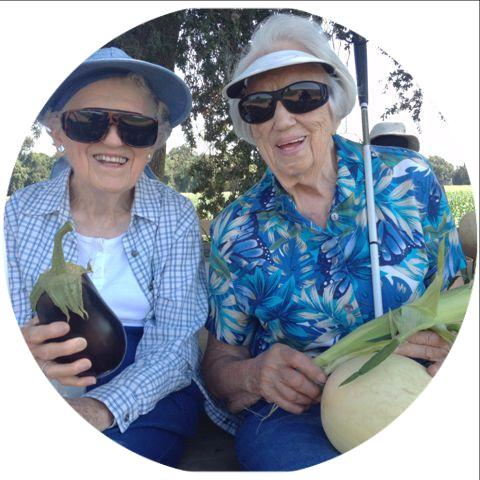 Two female seniors sit together wearing a blue plaid shirt and blue flowered shirt while holding corn_ eggplant and a cane.