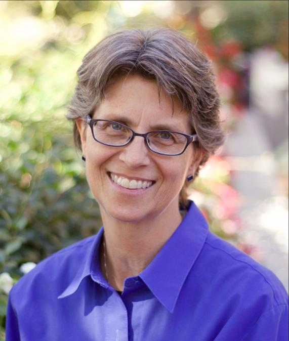 Executive Director Shari Roeseler smiles wearing glasses and a purple button-down shirt.