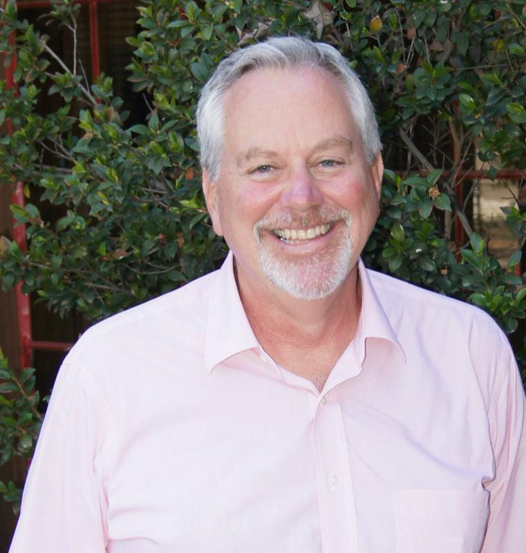 Society board member Gary Orr wears a pink shirt and smiles in front of a tree.