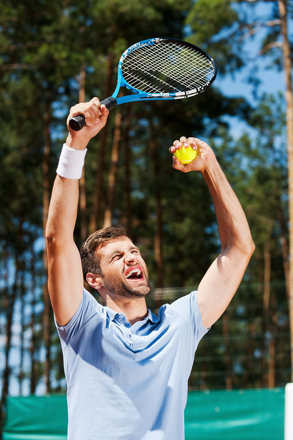 Happy young man in polo shirt raising his tennis racket up while standing on tennis court