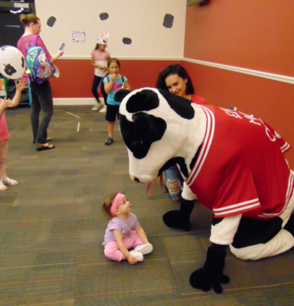 Photo of Chick-fil-a Cow and infant @ summer reading kick-off