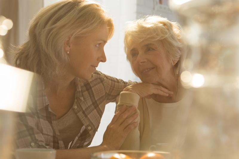 Middle aged female caregiver spending time with older lovely woman