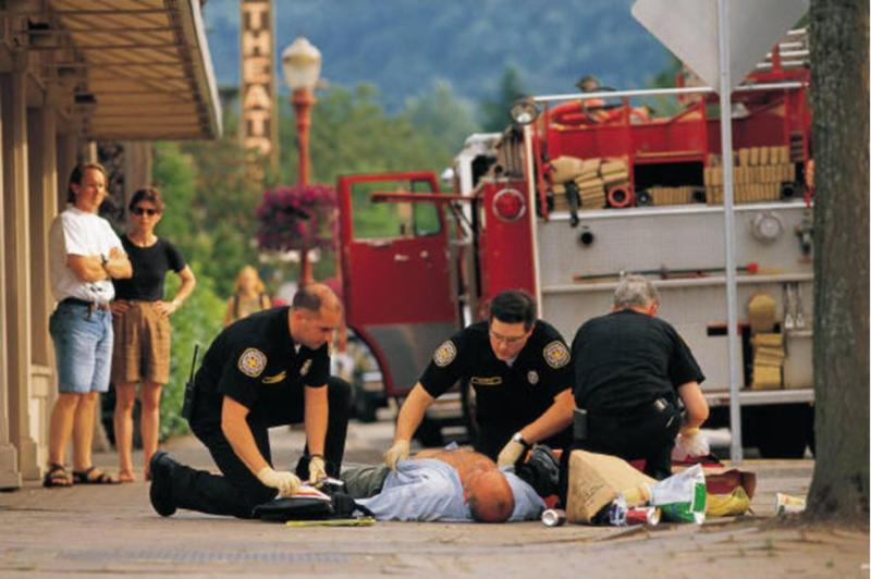 Photo of firefighters triaging a person who has collapsed on the sidewalk.man who