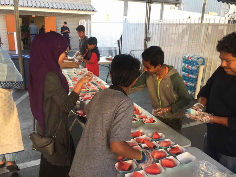 Photo of JYG mural processVolunteers preparing watermelon and dates for iftar