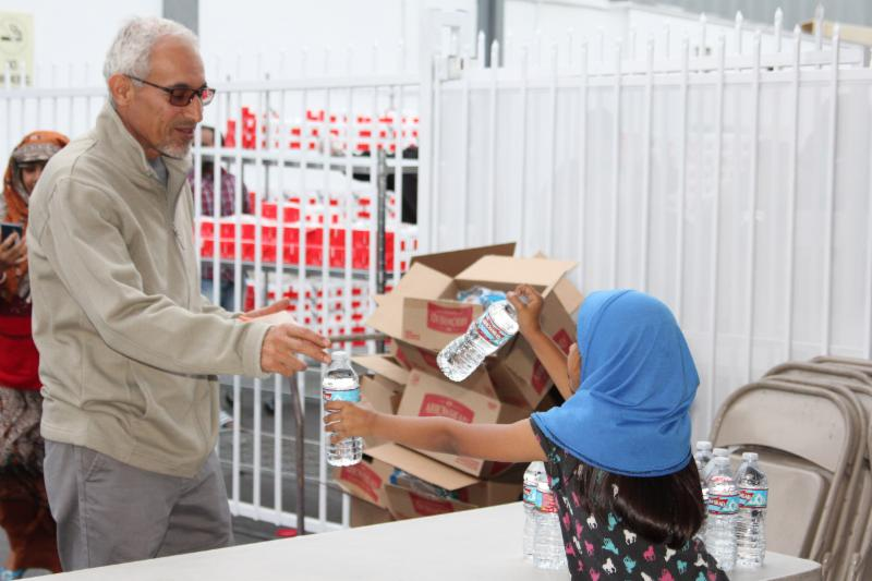 Photo of One of our young volunteers passing out water for people to break their fasts