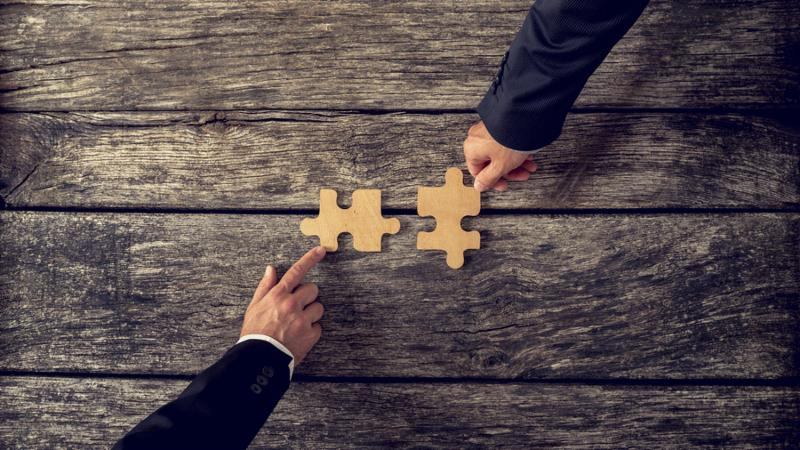 Retro style image of two business partners each placing one matching piece of puzzle on a textured wooden table. Conceptual of cooperation innovation and success.