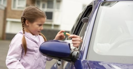 Girl taking candy at car